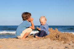 Brother and sister playing in sand at beach Royalty Free Stock Photography