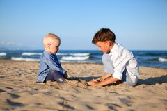 Brother and sister playing in sand at beach Stock Photography
