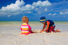 Brother and sister playing with sand on beach Royalty Free Stock Photography