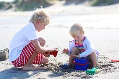 Brother and sister playing with sand on the beach Royalty Free Stock Photography