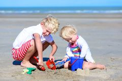 Brother and sister playing with sand on the beach royalty free stock images