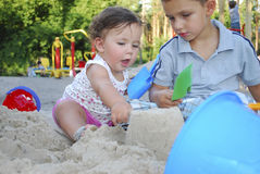 Brother and sister playing in the sand on the playground. Stock Photo