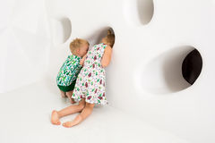 Brother and sister playing and smiling in a white studio Royalty Free Stock Images