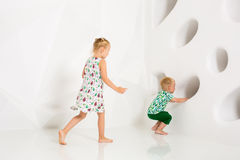 Brother and sister playing and smiling in a white studio Stock Image