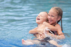 Brother and sister playing in the swimming pool Royalty Free Stock Images