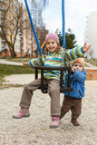 Brother and sister playing on the swing Stock Photography