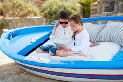 Brother and sister playing on tablet device Stock Images