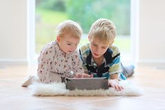 Brother and sister playing with tablet pc indoors. Smiling kids, teenager boy with toddler sister playing on tablet pc laying indoors on the tiles floor Stock Photography