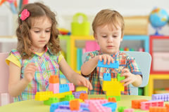 Brother and sister playing together. Brother and sister playing with colorful plastic blocks together Stock Photos