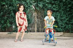 Brother and sister playing with a tricycle in cute traditional dress stock images