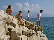 Brother and sister playing in the unusual rock. Four children playing in the unusual rock near the blue  Adriatic sea (Croatia Stock Photo