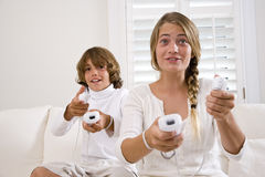 Brother and sister playing video games. Brother and sister playing video game together on white sofa Stock Photos