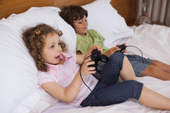 Brother and sister playing video games in bedroom Royalty Free Stock Image