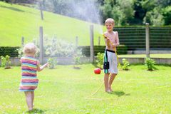 Brother and sister playing with water hose in the garden. Happy laughing children, young school boy and his adorable toddler sister, enjoying hot sunny summer royalty free stock images