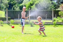 Brother and sister playing with water hose in the garden. Happy laughing children, young school boy and his adorable toddler sister, enjoying hot sunny summer stock image