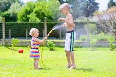Brother and sister playing with water hose in the garden. Happy laughing children, young school boy and his adorable toddler sister, enjoying hot sunny summer stock images
