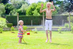 Brother and sister playing with water hose in the garden. Happy laughing children, young school boy and his adorable toddler sister, enjoying hot sunny summer royalty free stock image