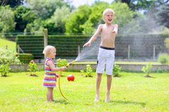 Brother and sister playing with water hose in the garden. Happy laughing children, young school boy and his adorable toddler sister, enjoying hot sunny summer stock photography