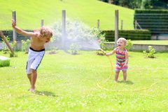 Brother and sister playing with water hose in the garden. Happy laughing children, young school boy and his adorable toddler sister, enjoying hot sunny summer Royalty Free Stock Photos