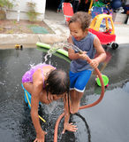 Brother and Sister Playing with Water Hose Royalty Free Stock Photo