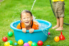 Brother and sister playing with water near a house at the day ti stock photos