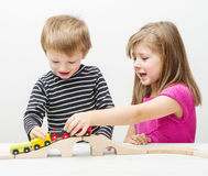 Brother and sister playing with wooden train Stock Photos