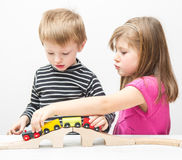Brother and sister playing with wooden train Stock Photography
