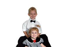 Brother and Sister Portrait. This big brother sits behind his little sister all dressed up with bowtie and cute dress Stock Photos
