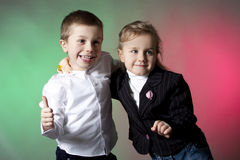 Brother and sister portrait. Portrait of brother and sister in the studio on red and green background Stock Photos
