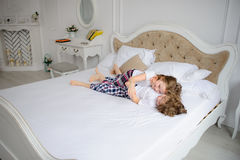 Brother and sister of primary school age play pranks on a bed. Stock Image