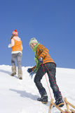 Brother and sister pulling sled up hill on ski slope Stock Image