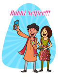 Brother and sister for Raksha Bandhan celebration. Time to take selfie, Happy brother and sister taking selfie on blue rays background for Indian festival Royalty Free Stock Image
