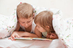Brother and sister, reading a bo Stock Photos