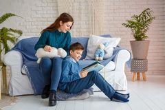 Brother and sister are reading a book royalty free stock photos