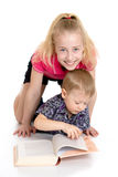 Brother and sister reading a book sitting on the Royalty Free Stock Image
