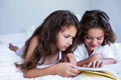 Brother and sister reading book together on bed Stock Photo