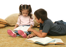 Brother and sister reading books on the floor Stock Photography