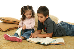Brother and sister reading books on the floor Stock Photo