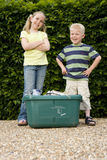 Brother (4-6) and sister (9-11) by recycling bin by hedge, smiling, portrait, low angle view Royalty Free Stock Photo