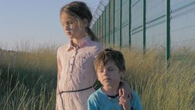 Brother and sister refugees are standing near a long high fence waiting for their parents. stock footage