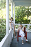 Brother and sister relaxing on porch Royalty Free Stock Photography