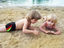 Brother and sister relaxing on sand near lake stock images