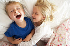 Brother And Sister Relaxing Together In Bed. Smiling Royalty Free Stock Images