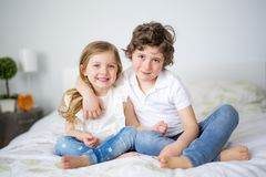 Brother And Sister Relaxing Together In Bed Stock Image