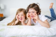 Brother And Sister Relaxing Together In Bed Stock Images