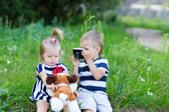 Brother and sister are resting in nature. The boy is taking pictures of an old girl in the open air. Little boy and girl are sitting on a stump in the forest Stock Photos