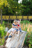 Brother and sister are resting in nature. Little boy and girl are sitting on a stump in the forest while outdoors in summer. Brother and sister are resting in Stock Images