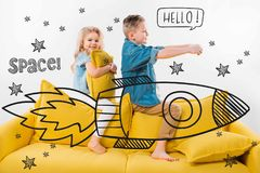 Brother and sister riding drawn rocket in space while sitting on sofa. At home Stock Photography
