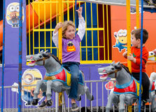 Brother and sister riding merry go round horses Stock Photo