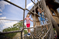 Brother and sister on rope ladder Royalty Free Stock Image
